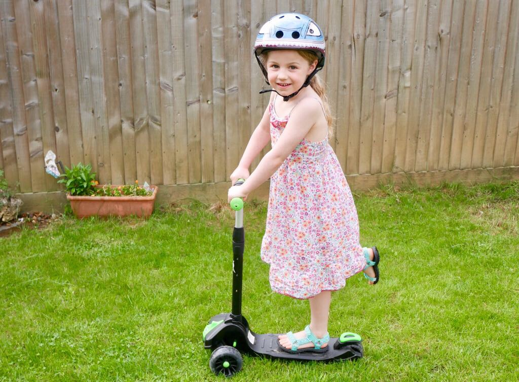 little girl in pretty dress scooting in the garden with a shark mini hornit lid helmet