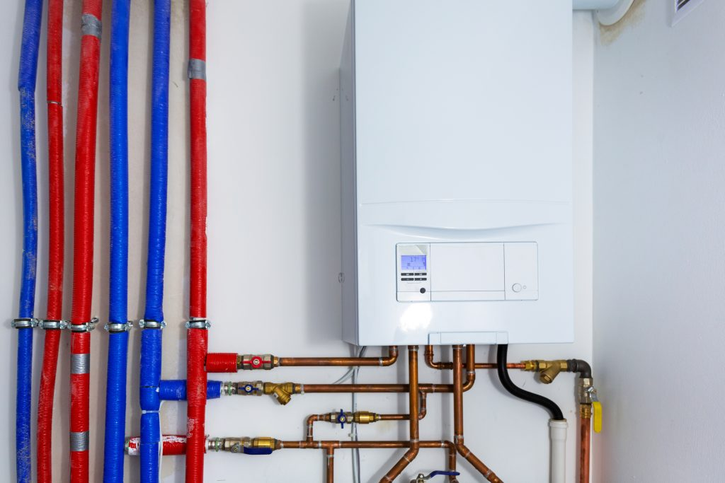 Pipes and boiler of gas heating system in the house